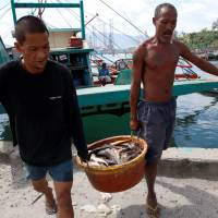 Fishermen, just returned from fishing in the disputed Scarborough Shoal, unload fish from a boat in the Philippines port of Subic on Tuesday. | REUTERS