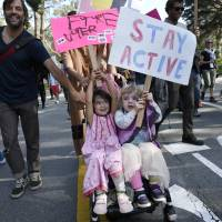 Two girls hold up signs while riding in a stroller during an anti-Trump march through San Francisco's Golden Gate Park on Sunday. | AP