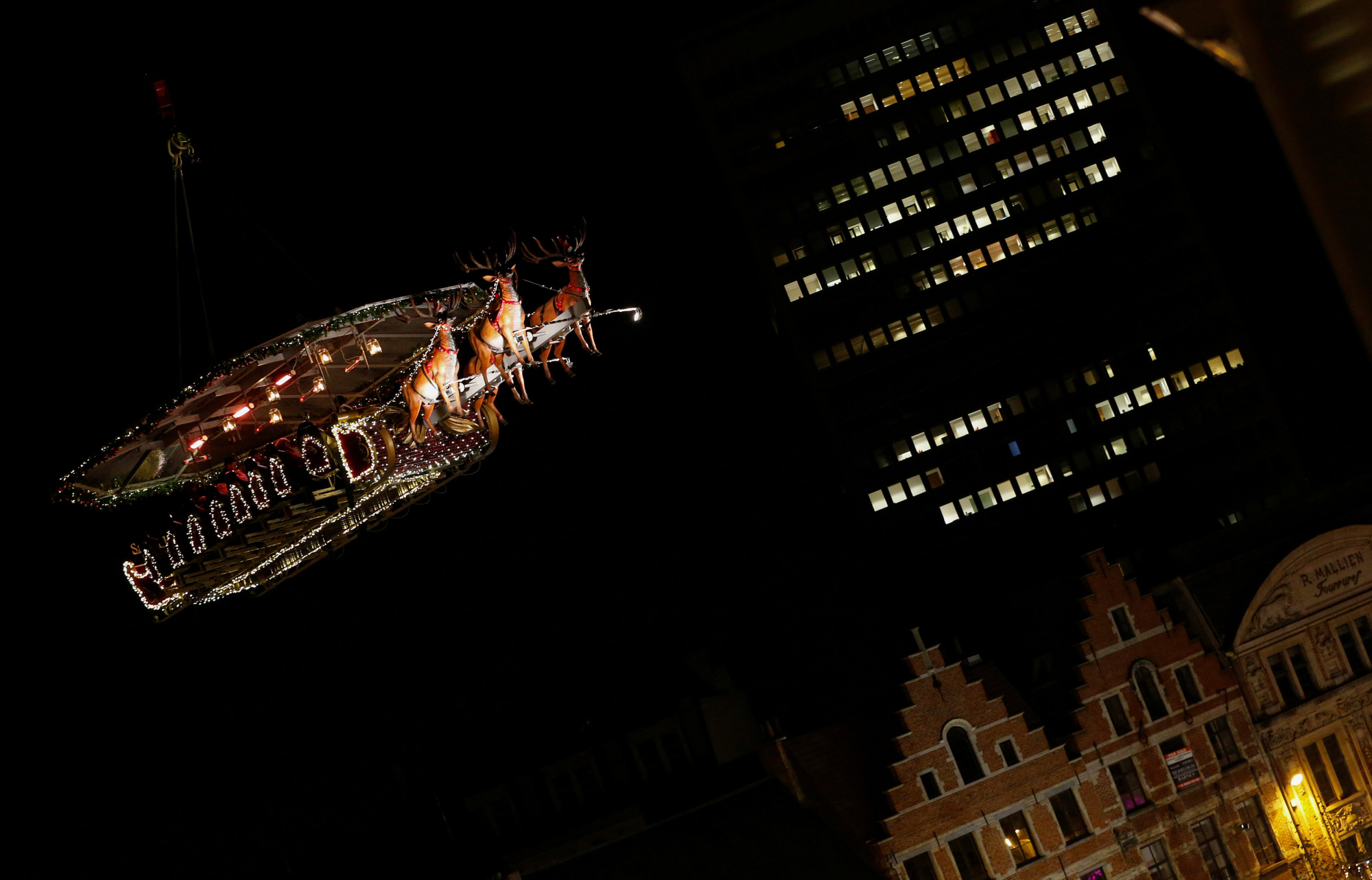 'Santa in the Sky,' a decorated dining platform lifted by a crane, appears to fly over Brussels on Friday. | REUTERS