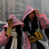 Protesters makes their way to join a demonstration calling for South Korean President Park Geun-hye to step down amid snowy weather in Seoul on Saturday.   REUTERS