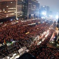 South Koreans hold candles during a rally against President Park Geun-Hye on a main street in Seoul on Saturday.   POOL / VIA REUTERS