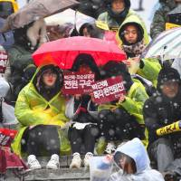 Protesters hold banners calling for the resignation of South Korean President Park Geun-Hye, before a mass anti-government rally in central Seoul on Saturday.   AFP-JIJI