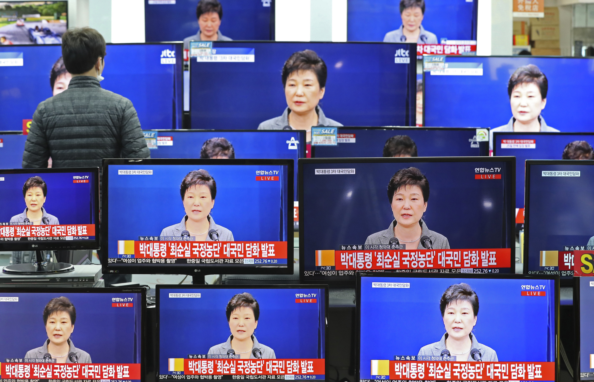 TV screens display the live broadcast of South Korean President Park Geun-hye's public announcement at an electronic shop in Seoul on Tuesday. | AP