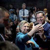 Democratic U.S. presidential candidate Hillary Clinton takes a photograph with a member of the audience after speaking in Manchester, New Hampshire, on Sunday. | AP