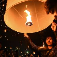 People hold on to paper lanterns to mark the annual Yi Peng festival in the popular tourist city of Chiang Mai in northern Thailand on Nov. 14. | AFP-JIJI