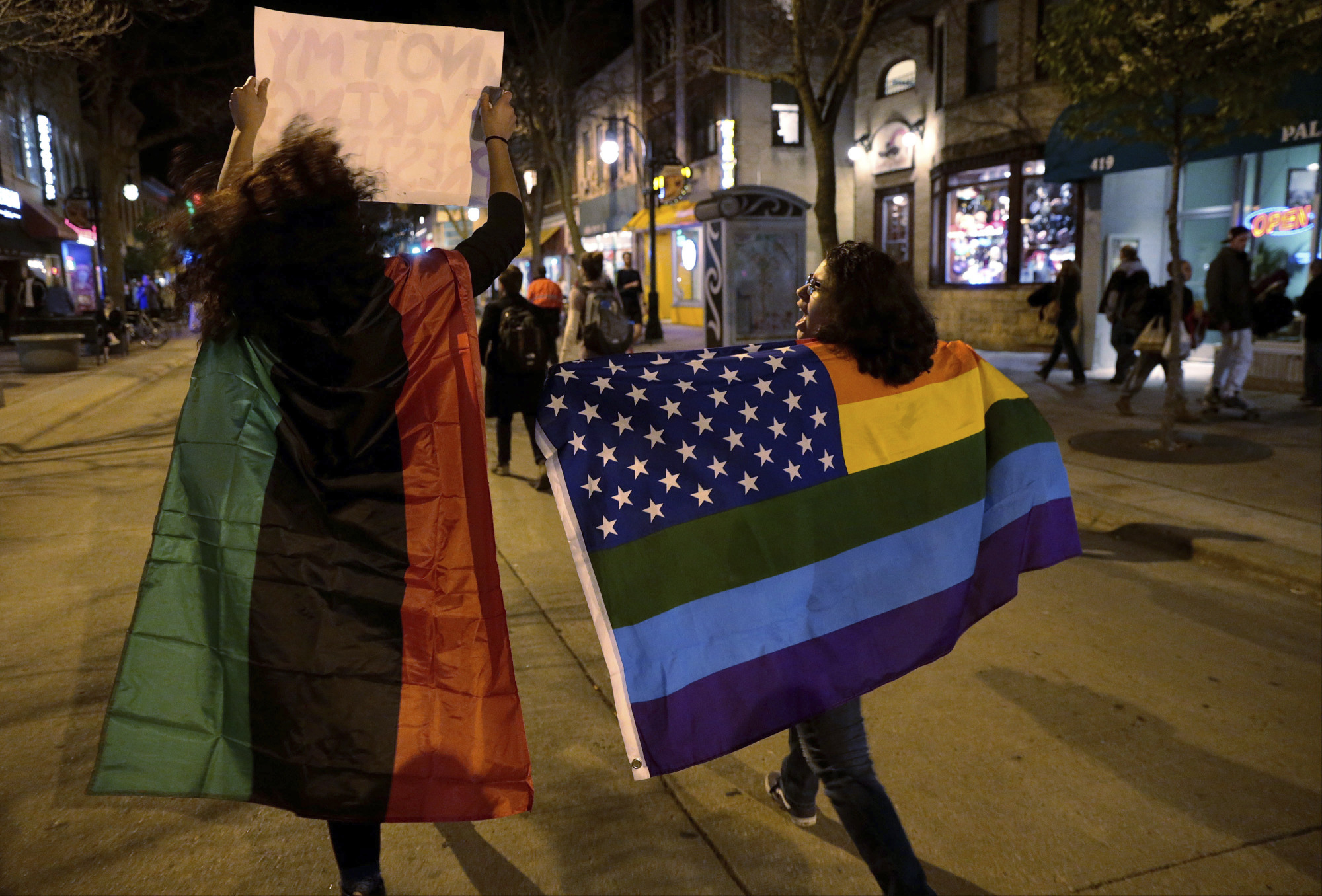 Two of a few thousand protesters, one holding a rainbow-colored flag, march up State Street from UW-Madison's Bascom Hall to the State Capitol, protesting President-elect Donald Trump in Madison, Wisconsin, on Nov. 10. | MICHAEL P. KING / WISCONSIN STATE JOURNAL VIA AP