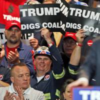 Coal miners wave signs as Republican presidential candidate Donald Trump speaks during a May rally in Charleston, West Virginia. Trump's election could signal the end of many of President Barack Obama's signature environmental initiatives. Trump has said he loathes regulation and wants to use more coal and expand offshore drilling and hydraulic fracturing. | AP