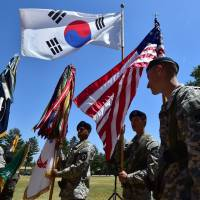 American soldiers hold the South Korean and U.S. flags before a joint ceremony at a U.S. Army base in Uijeongbu, just north of Seoul, in June 2015. | AFP-JIJI