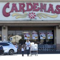 Customers exit Cardenas supermarket, where an advance polling station for the U.S. presidential election was allowed to remain open late on Friday, in an east side neighborhood of Las Vegas Tuesday. Republican Donald Trump sued the registrar of voters in Clark County, Nevada, over the polling place. | REUTERS