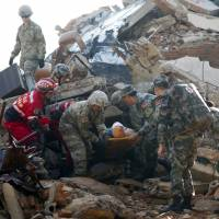 Soldiers from Chinese People's Liberation Army's Southern Theater Command Army and the U.S. Army Pacific carry an injured man as they conduct a search-and-rescue operation at a mock collapsed building during the U.S.-China Disaster Management Exchange drill at a PLA's training base in Kunming, southwestern China, on Friday. | AP