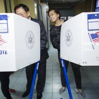 Nancy Liu watches her husband, John (center), as he is helped by a Chinese translator at a polling station in Queens, New York, on Tuesday. Born in Taiwan, John and Nancy immigrated to the United States 38 years ago, and they voted for the first time in an American election this week. | AP