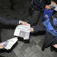 Extra edition of The Japan Times, being passed out in Yurakucho, Tokyo. | YOSHIAKI MIURA