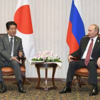Prime Minister Shinzo Abe and Russian President Vladimir Putin hold a meeting in Lima on Saturday. | KYODO