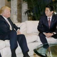 Prime Minister Shinzo Abe sits down with U.S. President-elect Donald Trump in New York on Thursday in their first meeting since Trump's election. | AFP-JIJI