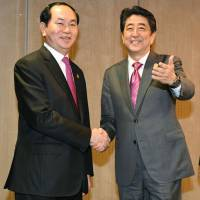 Vietnamese President Tran Dai Quang and Prime Minister Shinzo Abe get together for a meeting in Lima on Sunday.   KYODO