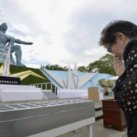 A woman prays at Nagasaki Peace Park on Aug. 9 this year, on the 71st anniversary of the 1945 atomic bombing on the city of Nagasaki. | KYODO