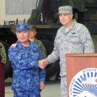 Lt. Gen. Jerry Martinez, commander of U.S. forces in Japan, shakes hands with Katsutoshi Kawano, chief of the Self-Defense Forces' Joint Staff, after a joint news conference at the U.S. military base in Iwakuni, Yamaguchi Prefecture, on Thursday. | KYODO