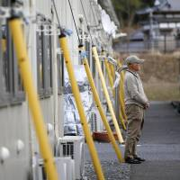 An elderly resident looks into the distance at temporary housing in Ishinomaki, Miyagi Prefecture, in March 2015. | KYODO