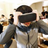 Keio University students wear virtual reality headsets to experience what it is like to have dementia at an event in Funabashi, Chiba Prefecture, on Oct. 27. | KYODO