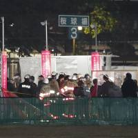Firefighters are seen at Tokyo Design Week in Tokyo's Meiji Jingu Gaien area on Sunday after an exhibit caught fire. A 5-year-old boy died and two men suffered injuries. | KYODO