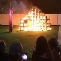 The wooden jungle gym installation at the Tokyo Design Week art event is seen in flames on Sunday in this photo supplied by a visitor. | KYODO