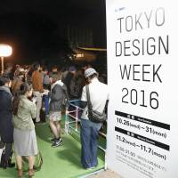 Visitors to Tokyo Design Week wait anxiously for news after a fire erupted in an exhibit at the event site in Tokyo's Meiji Jingu Gaien area on Sunday afternoon. | KYODO