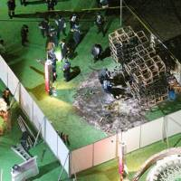 In this photo taken Sunday night from a Kyodo News helicopter, police officers can be seen examining the scene of a fire at the Tokyo Design Week site in Tokyo's Meiji Jingu Gaien area.   KYODO