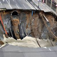 A huge sinkhole is seen Tuesday at an intersection near JR Hakata Station in downtown Fukuoka.   KYODO