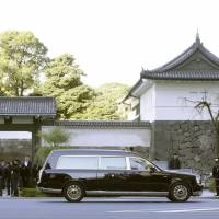 A hearse carrying the body of Prince Mikasa, who passed away last month at the age of 100, passes the Imperial Palace in Tokyo's Chiyoda Ward on Friday morning after departing his residence on the grounds of the Akasaka Estate in Minato Ward en route to Bunkyo Ward's Toshimagaoka Cemetery. | KYODO