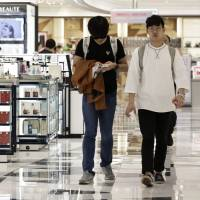 Customers walk through the cosmetics section of the Lotte Duty Free Shop in the Tokyu Plaza Ginza shopping complex in Tokyo's Ginza district in April.   BLOOMBERG