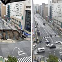 A huge sinkhole opens up beneath a street near JR Hakata Station in the city of Fukuoka on Nov. 8, and then the area reopens to people and vehicles Tuesday morning. | KYODO