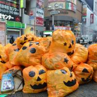 Jack-o'-lantern plastic bags filled with trash left by costumed partygoers are piled up on a sidewalk in Shibuya Ward, Tokyo, early Tuesday. | KYODO