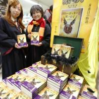 Costumed fans hold copies of the Japanese translation of J.K. Rowling's 'Harry Potter and the Cursed Child,' at a bookstore in Hachioji, Tokyo, early Friday right after the eighth tale in the fantasy series was released. | KYODO