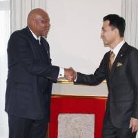 Visiting Lesotho King Letsie III shakes hands with Michio Umemoto, the leader of nonprofit group Stone for Peace Association of Hiroshima, after receiving a paving stone that survived the 1945 U.S. atomic bombing at a ceremony Thursday in Tokyo. | KYODO