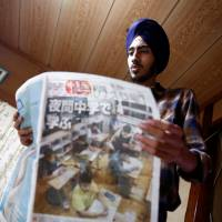Gursewak Singh holds a Japanese newspaper at his home in Matsudo, Chiba Prefecture, on Sept. 25. | REUTERS