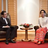 Myanmar's de facto leader Aung San Suu Kyi consults with Foreign Minister Fumio Kishida at a hotel in Tokyo on Thursday. | AFP-JIJI