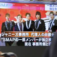 Passersby watch the news of SMAP's breakup on a TV screen in Tokyo. | KYODO