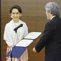 Myanmar's leader Aung San Suu Kyi receives an honorary doctorate from Kyoto University President Juichi Yamagiwa at its campus in the city of Kyoto on Thursday. | KYODO