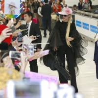 Lady Gaga is cheered by fans upon her arrival at Narita International Airport on Tuesday. | AP