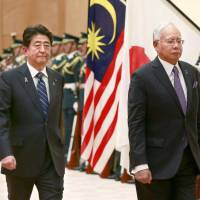Malaysian Prime Minister Najib Razak (right), accompanied by his Japanese counterpart Shinzo Abe, reviews a guard of honor prior to their meeting in Tokyo Wednesday. | AP