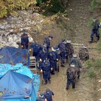 Police investigate a site in the mountains of the village of Chihayaakasaka, Osaka Prefecture, where the body of a small boy was found Tuesday. | KYODO