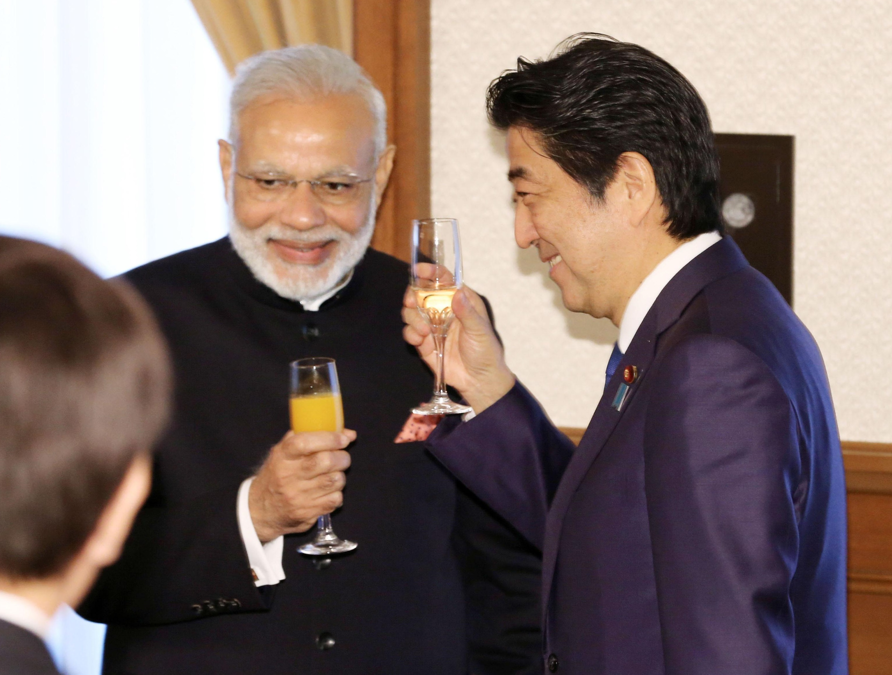 Visiting Indian Prime Minister Narendra Modi and Prime Minister Shinzo Abe make a toast during a luncheon Saturday in Kobe. Modi visited the city to inspect a plant assembling shinkansen bullet trains. | KYODO