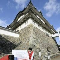 Officials place a sign warning on Friday in the city of Nagoya saying that the main building at Nagoya Castle could collapse in strong earthquakes. | KYODO
