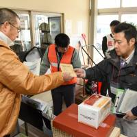 A resident (left) receives iodine tablets while taking part in a disaster drill Monday in Kyowa, Hokkaido. | KYODO