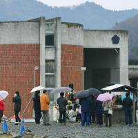 People visit Okawa Elementary School in the city of Ishinomaki, Miyagi Prefecture, last March. A huge tsunami that occurred on March 11, 2011, hit the school, claiming 74 lives. | KYODO