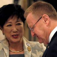 International Olympic Committee Vice President John Coates speaks with Tokyo Gov. Yuriko Koike following the Four-Party Working Group meeting in Tokyo on Tuesday. | REUTERS