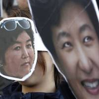 South Korean protesters wear masks of President Park and her confidante at a rally in downtown Seoul on Wednesday. | AP