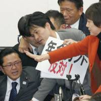 Opposition lawmakers harangue Hideki Niwa (seated), chairman of the Lower House health, labor and welfare committee, at a session Friday before the ruling block rammed a pension bill through the panel without their consent. | KYODO