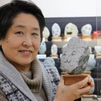 Yoshiko Hayama, curator of Chichibu Chinsekikan (Chichibu Museum of Rare Rocks), holds an exhibit at the museum in Chichibu, Saitama Prefecture, on Oct. 25. | KYODO