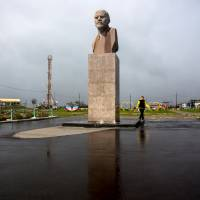 A woman walks past a statue of Soviet state founder Vladimir Lenin in Yuzhno-Kurilsk, the main settlement on the island of Kunashiri, part of the Japanese-claimed Northern Territories, in mid-September. | REUTERS